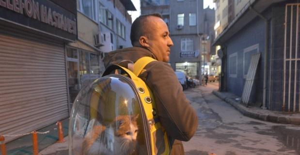 Sahiplendiği kediyi sırt çantasında gezdiriyor
